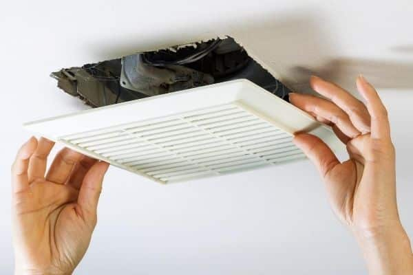 2 hands removing bathroom exhaust fan
