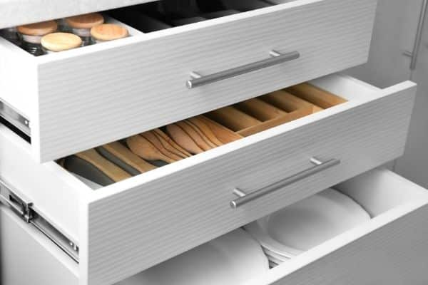 3 kitchen drawers opened with spices plates and utensils organized