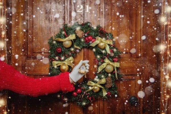 Christmas wreath on door snow falling white gloved hand holding small gold clock