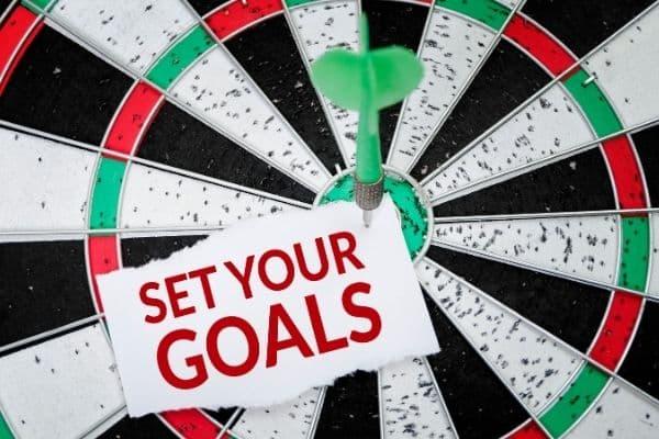 Dartboard with arrow in bullseye says SET YOUR GOALS