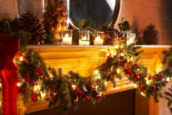Mantle with Christmas Decorations wreath Candles lit