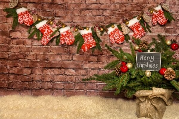 Mittons and Stockings and Pine Boughs hanging on a brick wall