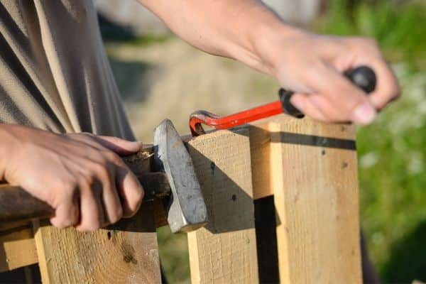 Repairing fence With Hammer and Crowbar
