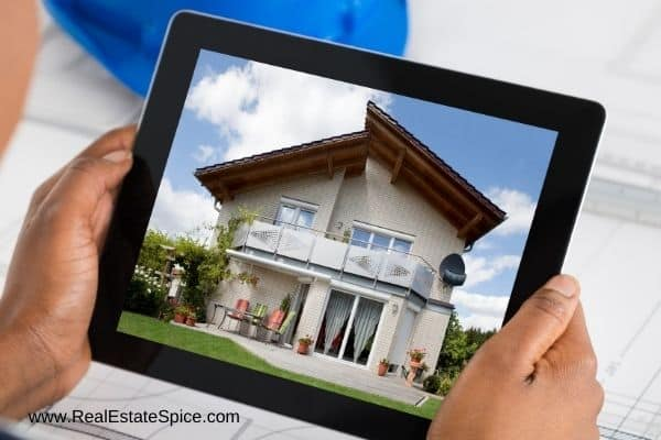 person holding a tablet w a house on the screen